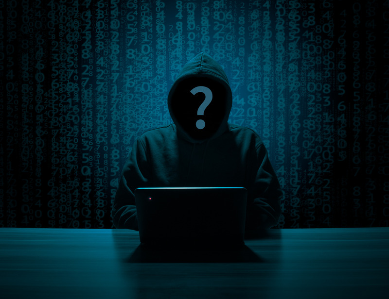 An unknown person with a hood up and a question mark where their face should be sitting in front of a laptop on a table. The background is strings of coding.