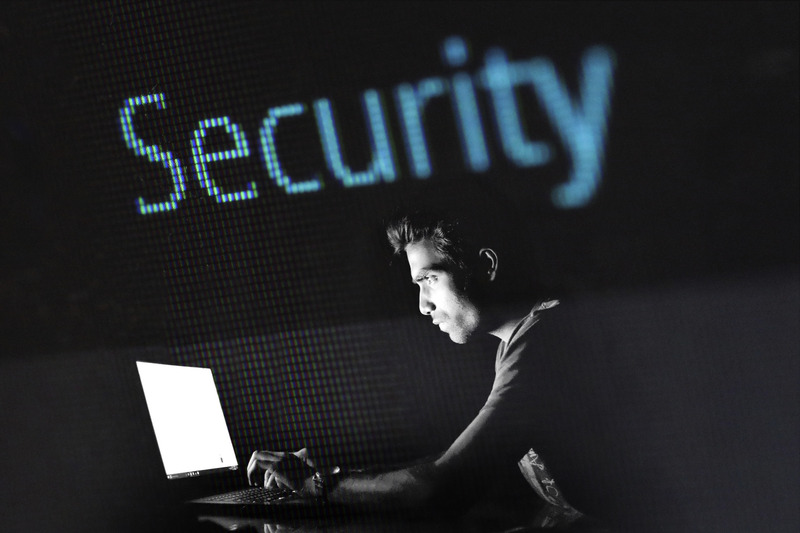 A man on a laptop in black and white with the word 'Security' over his head in blue.
