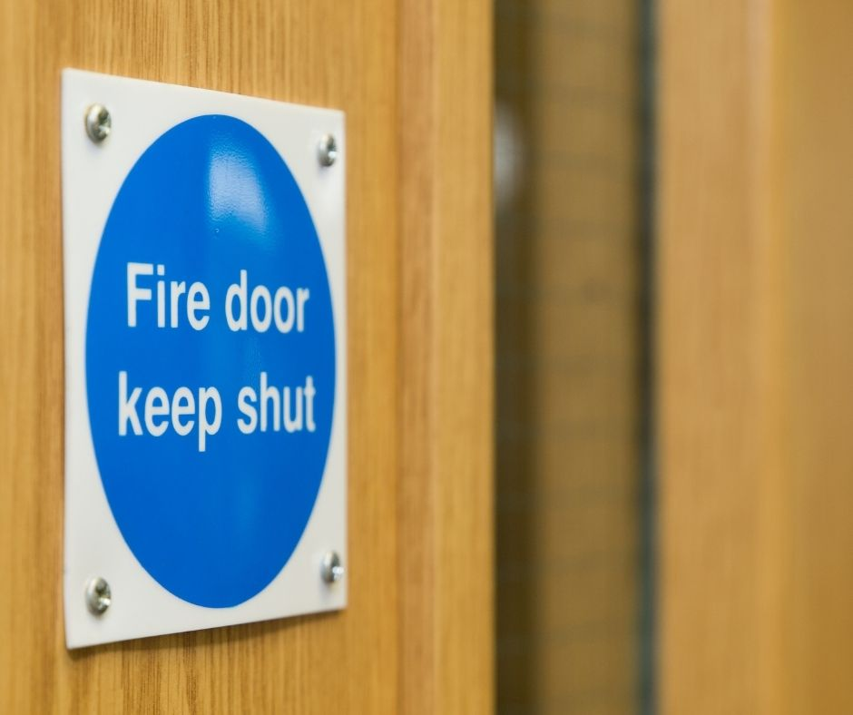 Close up of a fire door on the panel that reads 'Fire Door Keep Shut'