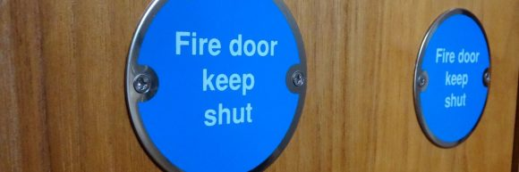 Close up of blue 'fire door keep shut' sign with white writing