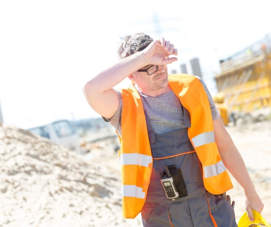 Tired construction worker wiping sweat from his brow on a sunny day