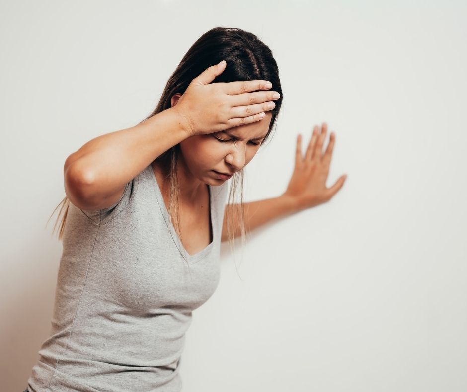 Woman with a headache holding her forehead with one hand and propping herself against a wall with the other