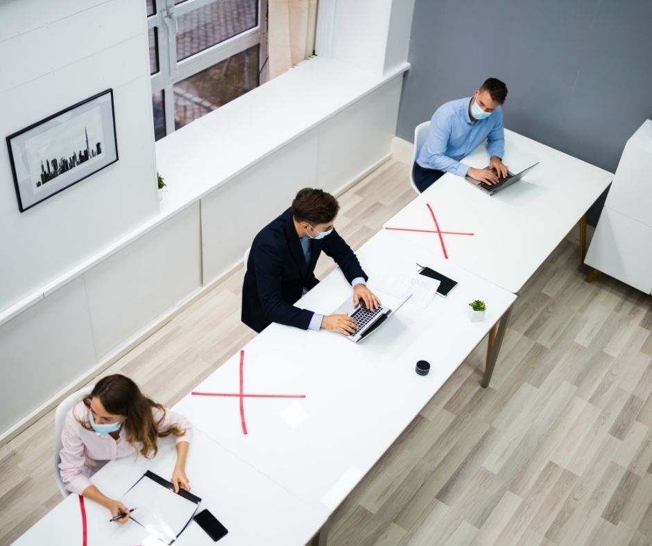 three people sat on a long desk, social distancing