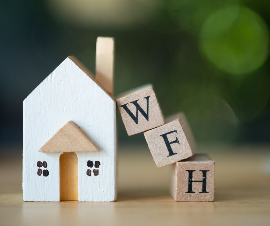 Miniature wooden house with stacked up wooden blocks spelling 'WFH'