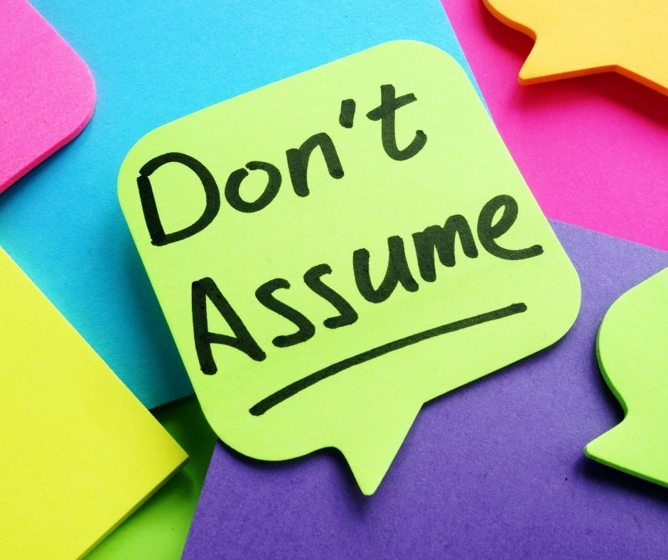 Speech bubble shaped post it note that says 'don't assume'