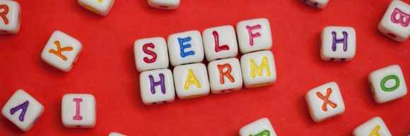 Letter dice spelling out 'self harm'