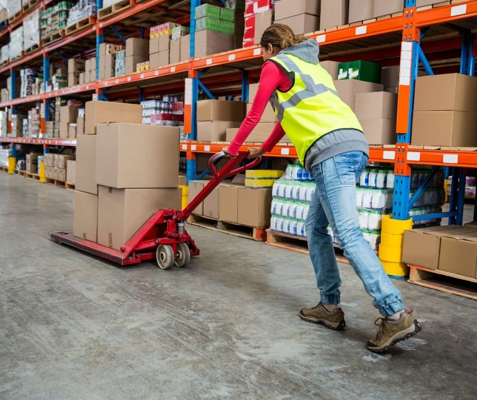 Worker pushing boxes in a warehouse