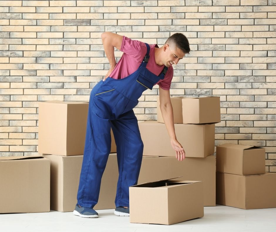 Man surrounded by cardboard boxes, hunched over holding his back in pain